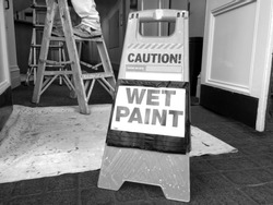 Hazard sign reads: Caution Wet Paint. Renovation and construction concept