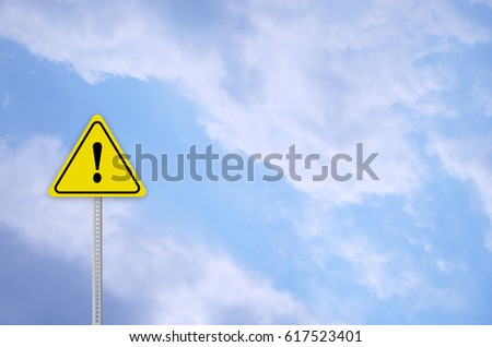 hazard warning attention sign with cloudy sky #617523401