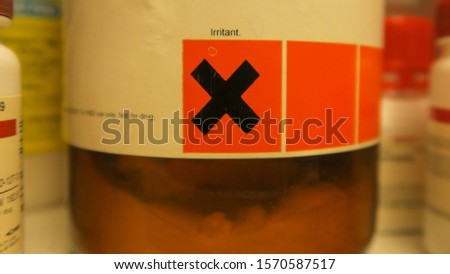 Hazardous chemical powder with the irritant hazard sign and an out of focus effect