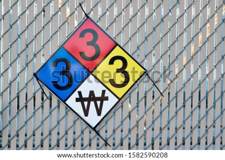 Hazardous Materials Classification Sign attached to a wire fence. The colors represent fire, health and reactivity hazards, the numbers are severity. Bottom W icon means use no water.