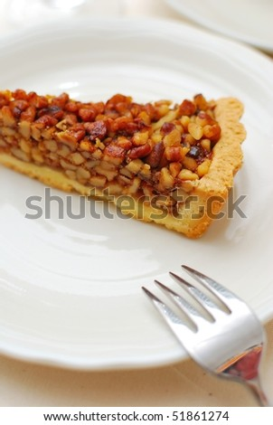 Hazel nut tart with fork on white plate. For concepts such as food and beverage, diet and nutrition, and healthy eating.