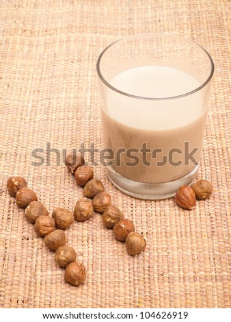 Hazelnut milk in glass with nuts on burlap