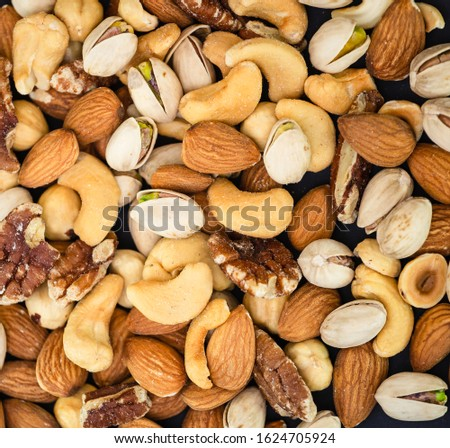 Hazelnut ,Pecan nut, Pistachio nut ,Peanuts nut,Almond nut mixed salt in a wooden plate is Protein food and healthy food for diet food on a black background.