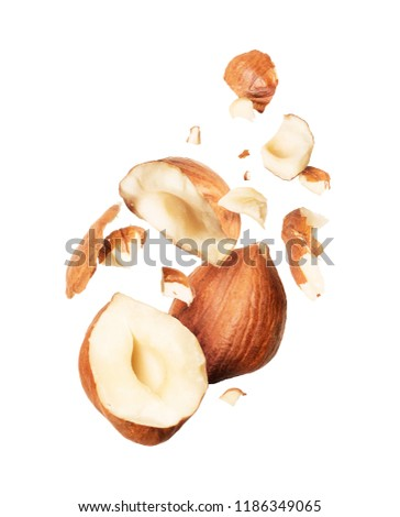 Hazelnuts crushed in the air close-up on white background