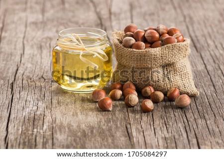 Hazelnuts, filbert in burlap sack and hazelnut oil in glass of bottle on rustic backdrop. heap or stack of hazelnuts. Hazelnut background, healty food Foto d'archivio ©
