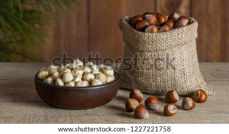 Hazelnuts, filbert in burlap sack and in brown bowl on rustic wooden table. heap or stack of hazelnuts. Hazelnut background, healty food Foto d'archivio ©