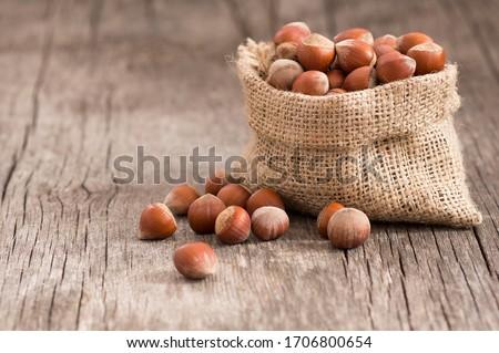 Hazelnuts, filbert in burlap sack on rustic wooden table. heap or stack of hazel nuts. Hazelnut background, healty food ( corylus ) Foto d'archivio ©
