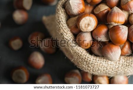 Hazelnuts, filbert in burlap sack on wooden backdrop. heap or stack of hazelnuts. Hazelnut background, healty food