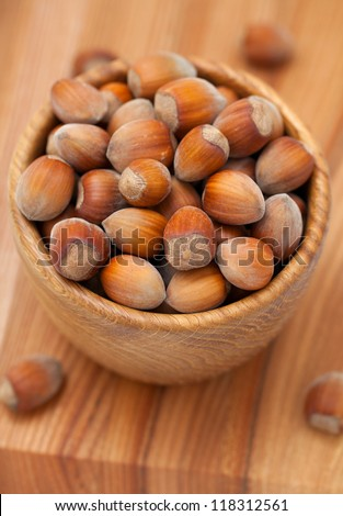 Hazelnuts in a wooden bowl on a table