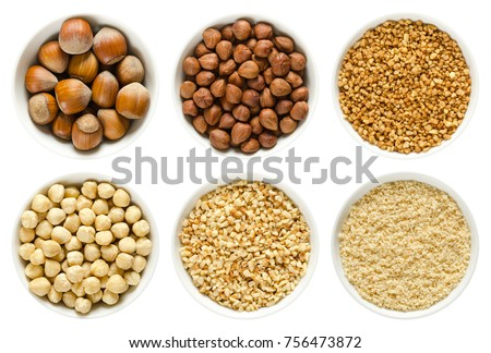 Hazelnuts in white bowls. Whole nuts, shelled, blanched and roughly chopped. Ground hazelnuts and hazelnut brittle. Corylus avellana. Macro photo, close up, from above, isolated, on white background. #756473872