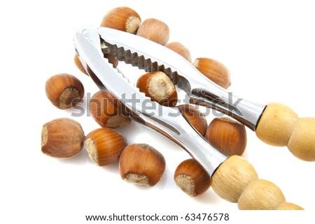 Hazelnuts with nut cracker isolated over white