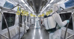 HazMat team in protective suits decontaminating metro car during virus outbreak. Coronavirus COVID-19