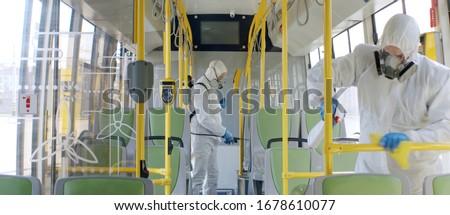 HazMat team in protective suits decontaminating public transport, bus interior during virus outbreak Сток-фото ©