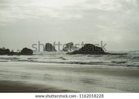 Hazy Coastline with Dark Rock Formations, Bright Day