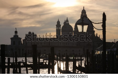 Hazy dusk, sunset clouds on Santa Maria Della Salute and Gondola silhouettes, Venice