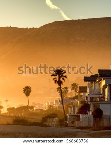 Hazy golden sunset on Malibu beach, California