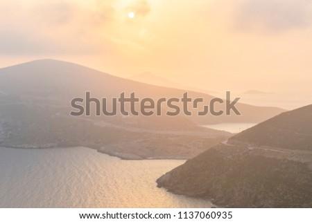 Hazy morning view of Fourni coastline and Agios Minas island in the distance, Greece.