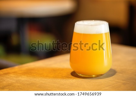 Hazy NEIPA New England IPA pale ale beer, on wood surface, rich frothy foam head with copy space Foto stock ©