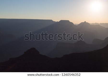 Hazy silhouettes of Grand Canyon features at sunrise from South Rim