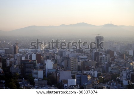 Hazy skyline of Mexico City at dawn, smog covering suburban hills - stock photo
