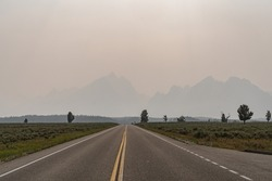 Hazy smoke in the air from nearby summer wildfires in the Grand Teton National Park in Wyoming. Poor visibility for mountains