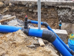 HDPE plastic tubes for drink water. Reneval potable water system in the city. Laying drink water pipe at the corner of a flat house