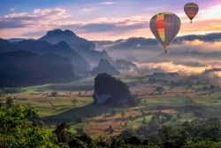 HDR beautiful scenary in the north part of Thailand over the valley of mountain at sun rise beautiful color of mist, hot air balloon flying in sky (selective focus and white balance shifting applied)