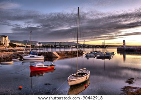 HDR effect - Boats in Harbour with Lighthouse and reflection in the water during sunrise in Port st. Mary on the Isle of Man