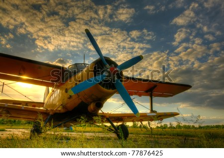 HDR foto of an old airplane on green grass and sunset background