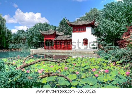 HDR image of a Chinese temple in a garden behind a pool of water
