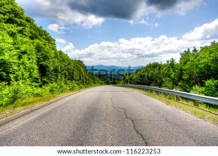 HDR image Of Country Road in the mountains without road vehicle, and in the background the mountains of the Eastern Townships in Quebec on ??a cloudy day.