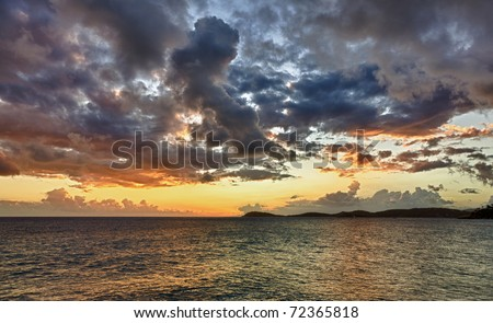 HDR impression of a sunset over the ocean with a distant island on the horizon