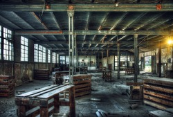 HDR - old abandoned factory interior with wooden tables and boxes