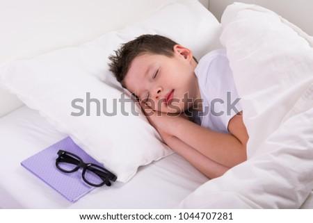 he boy is sleeping on the white bed next is the book and glasses