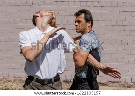 he defender dodges the attack, holding the attacker by the elbow. Close-up. Martial arts instructors demonstrate self-defense techniques of Krav Maga