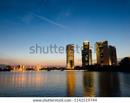 he dusk of the dusk attracts the back of the four buildings that stand tall in front of a lake. it is very interesting. #1142519744