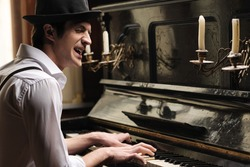 He�¯�¿�½ got creative soul. Handsome young men playing piano and singing