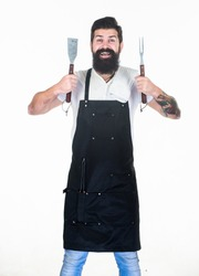 He is a great cook. Happy grill cook with cooking utensils. Bearded man holding fork and spatula for cooking and serving barbecue. Master cook wearing grilling apron. Chief cook in workwear. Cookout.
