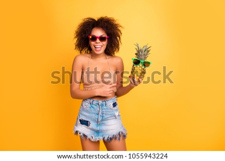 He is a humorist! Cheerful joyful with curly lush unruly hairdo afro with bronze tanned skin woman wearing knitted summer top and denim skirt is holding a pineapple, isolated on yellow background #1055943224