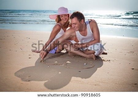 He is drawing for her a heart on the sand