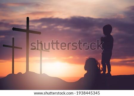 He is risen.Jesus Christ cross and worship with faith in Good friday.Silhouette kid child pray in Easter, Good friday.jesus christ in holy cross on resurrection sunday. Worship jesus, christian, pray.