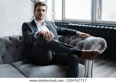 He knows all of your secrets. Handsome young man in white shirt looking away and smiling while sitting on sofa.