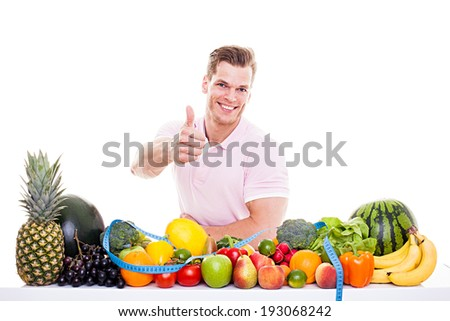 He knows what's good for you! - Handsome muscular man sitting behind a table full of vegetables and fruits and showing thumb up, isolated on white