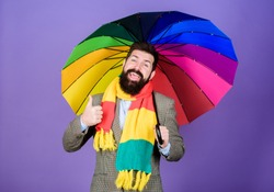 He likes rain. Bearded man giving thumbs up hand gesture to rain weather. Hipster holding colorful umbrella. Rain man. The colorful umbrella never fails to catch the eye.