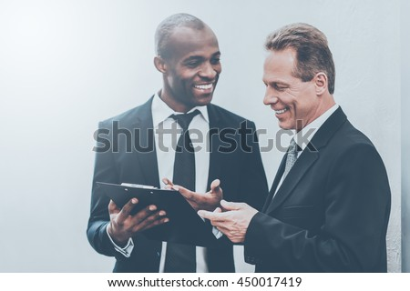 He needs an expert advice. Two cheerful business men looking at the note pad and gesturing