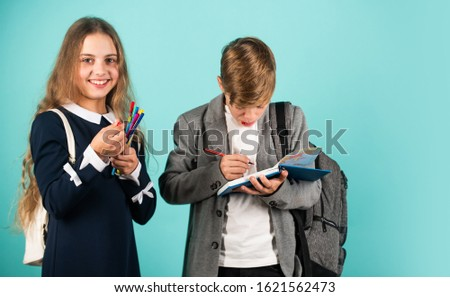 He needs help with homework. Little children do homework assignment. Small girl and boy hold pens and homework diary. School homework club. Education and study.