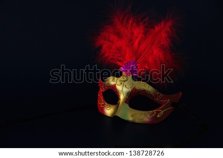 he/she chewed of golden carnival with red feathers on dark bottom