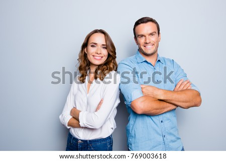 He vs she happy together. Close up portrait of attractive, caucasian, lovely, cute, adult couple in casual outfit  looking at camera standing with crossed arms over grey background