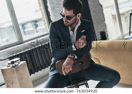 He will melt your heart. Handsome young man in full suit and eyewear looking away while sitting on the stool #763034920