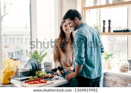 He will never let her go. Beautiful young couple cooking dinner and drinking wine while standing in the kitchen at home